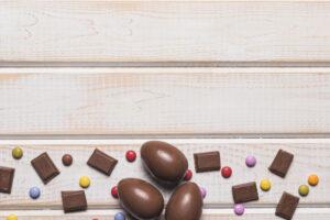 trozos-chocolate-huevos-pascua-caramelos-gemas-fondo-escritorio-madera_23-2148066738